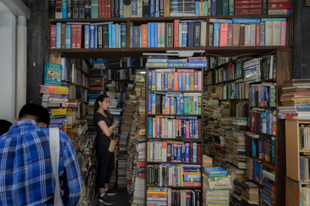 A woman looking at books surrounded by crammed stacks of used books and old bookshelves with a man in the foreground hunched over.