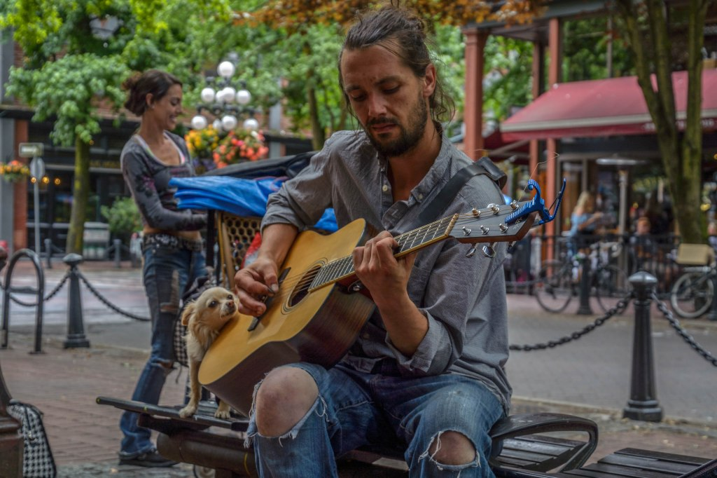 A man in ripped jeans at the knee and a rolled up dress shirt playing guitar, while a dog peeks around him and a woman is walking behind him in an urban setting.