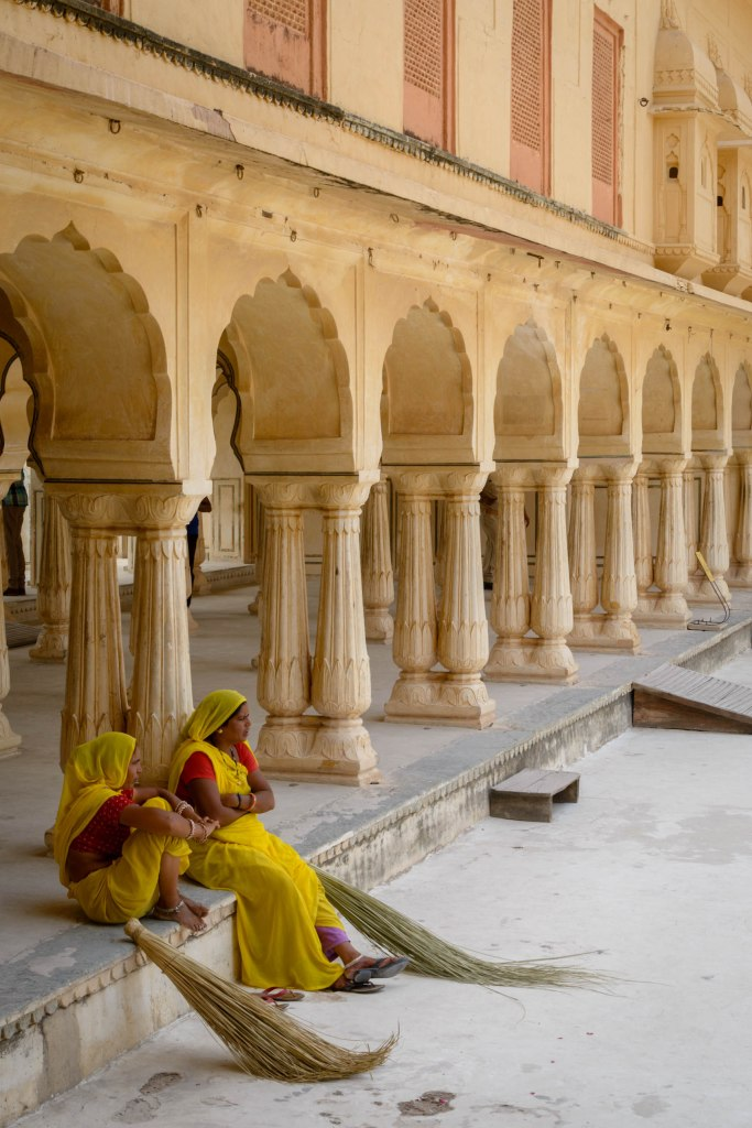 Two woman, with grass brooms, sitting on a step, clothed in bright yellow and red saris and shirts, against an arcade of arches and columns.