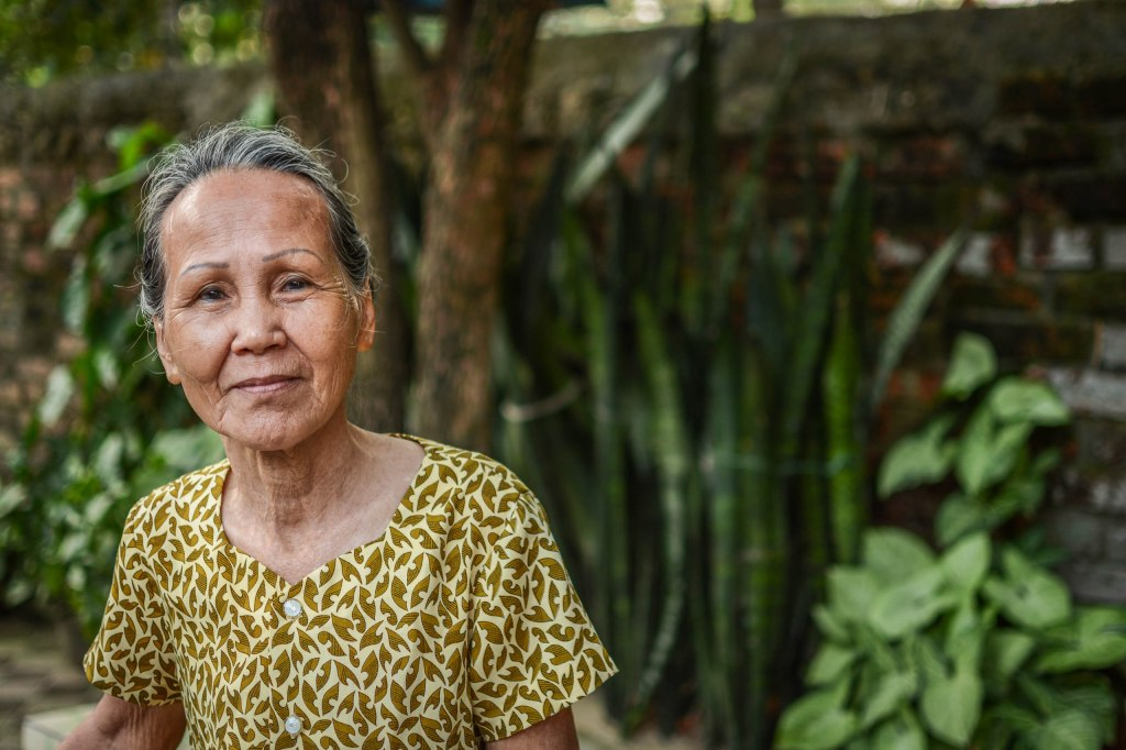 An elderly, smiling, Vietnamese woman in a green, leaf patterned top, in front of some trees and plants.