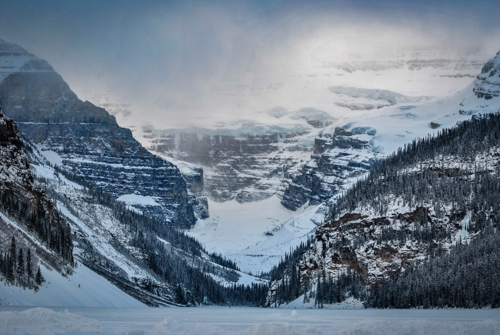A snow-laden mountain landscape of Lake Louise glacier and its surrounding pine trees, with fog rolling overhead.