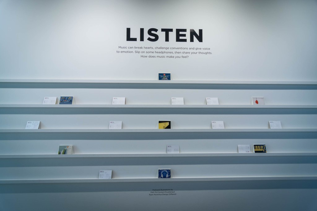 """Listen"" painted in block letters on a white wall with a quote beneath it and 5 skinny shelves on the wall holding sparsely spaced postcards."