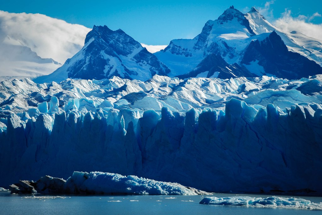 Blue, snow covered mountains and ice glacier covered with snow, clouds billowing in the distance and water in the foreground.