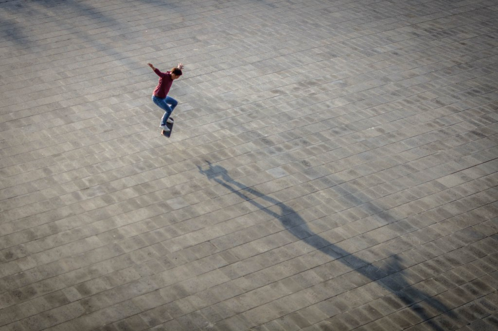 Skateboarder launching himself up in the air on his skateboard with his arms out for balance as the setting sun casts a long shadow on a pavement of patterned stone.