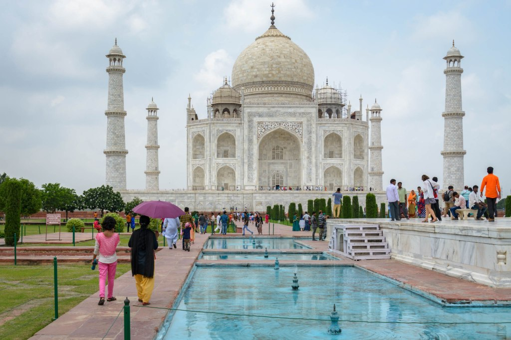 A view of the Taj Mahal on a partly cloudy day, with two woman walking beside blue reflecting pools and fountains, and people milling about.