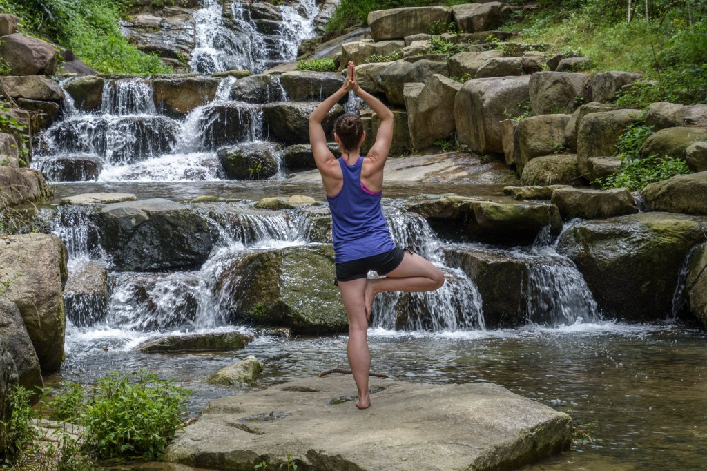 A woman in shorts and a tank top doing a yoga pose on one leg with the other leg tucked under and her hands pressed together over her head beside a small-tiered waterfall and surrounded by large rocks and greenery.