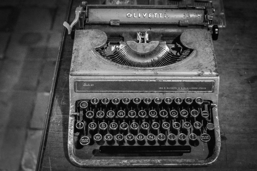 A vintage, dirty Olivetti Studio 42 typewriter on a table in black and white.