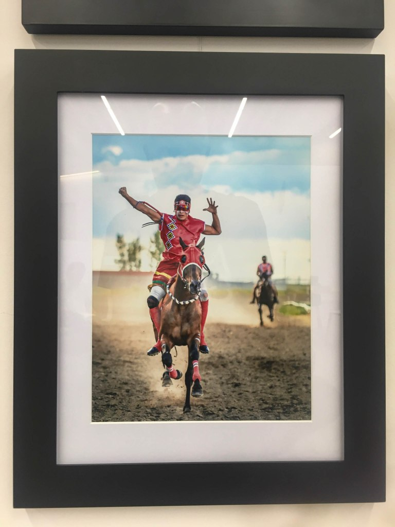 Framed picture of Indian Relay by Julie Vincent and Jason Lawrence at  a photo exhibit at the Calgary Public Library (August 2019).